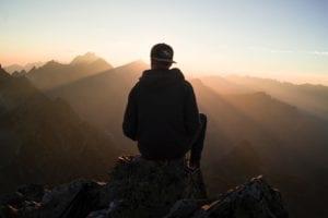 man sitting overlooking land