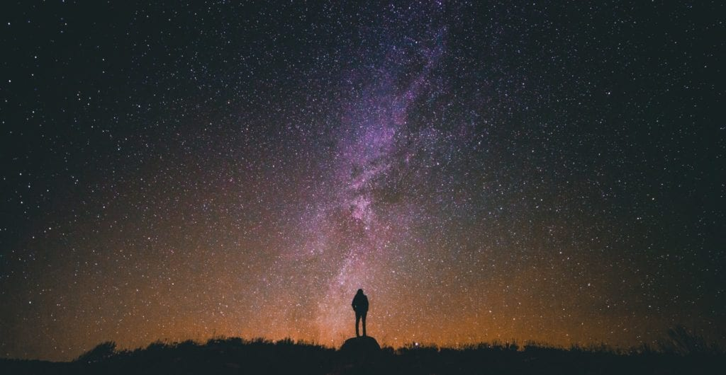 man standing looking at night sky